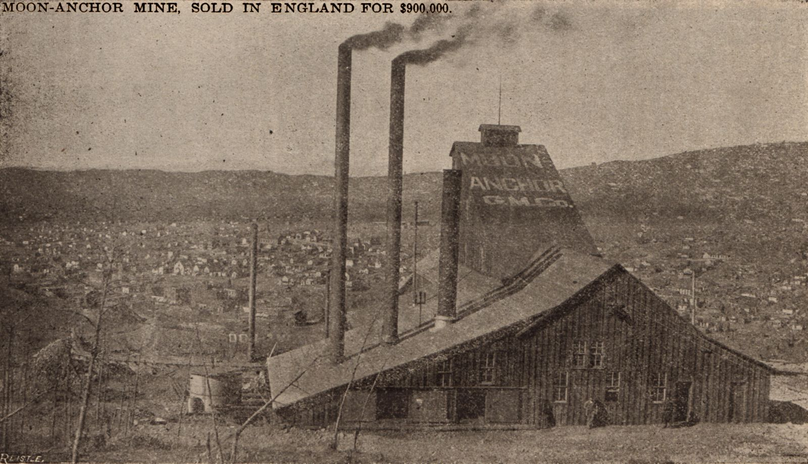 This sadly bad quality view shows the Mine looking at it from the east, showing it real close-up with the words Moon Anchor G.M. Co. clearly visible on the roof covering the head frame. You also see three sliding doors covering up two openings on the backside left - most likely for bringing in coal and other stuff. Further to the right, a couple of men is posing. This mine has in this view three smokestacks, various heights. In the background is the town of Cripple Creek barely seen in the bad print quality of this view, also part of the Short Line grade climbing Gold Hill is seen near lower left corner.