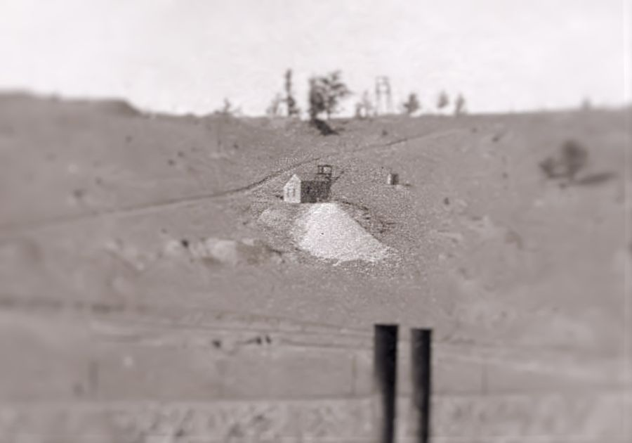 This cropped view is from a photo by A.J. Harlan, showing the Morning Glory mine up close. The two smokestacks seen in lower foreground belong to that mine. The railroad fill seen along the bottom of this view belongs to the Low Line, with the side spur up the Index mine climbing the hill below the little shaft house of the Union Bell mine almost at center of view.