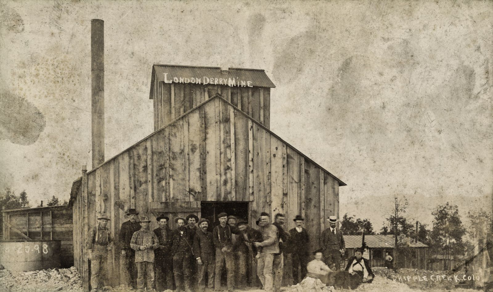 A group of miners pose at the doorway on the south gable end of what I believe to be the new shaft house after the fire earlier in 1898 that burned the older structure of the Londonderry Mine. Located on Ironclad Hill, at Midway, near Cripple Creek (Teller County), Colorado. The men wear work clothes and a couple of them seem to joke about a little as they are moving about, messing up the sharpness/focus of that part of the image. Two women sit on the ground in front of two well-dressed men. A woman stands with her hand on her hip in the doorway of a building in the distance on the right. The building is made from wood planks, has a corrugated tin roof, a smoke stack, a coal shed on the left with a tank for possible water in front of that shed. Outside the view to the right would a ore-house been located and also the balloon-loop of the Golden Circle at Vista Grande, also known as Midway as a Trolley stop on the High Line.
