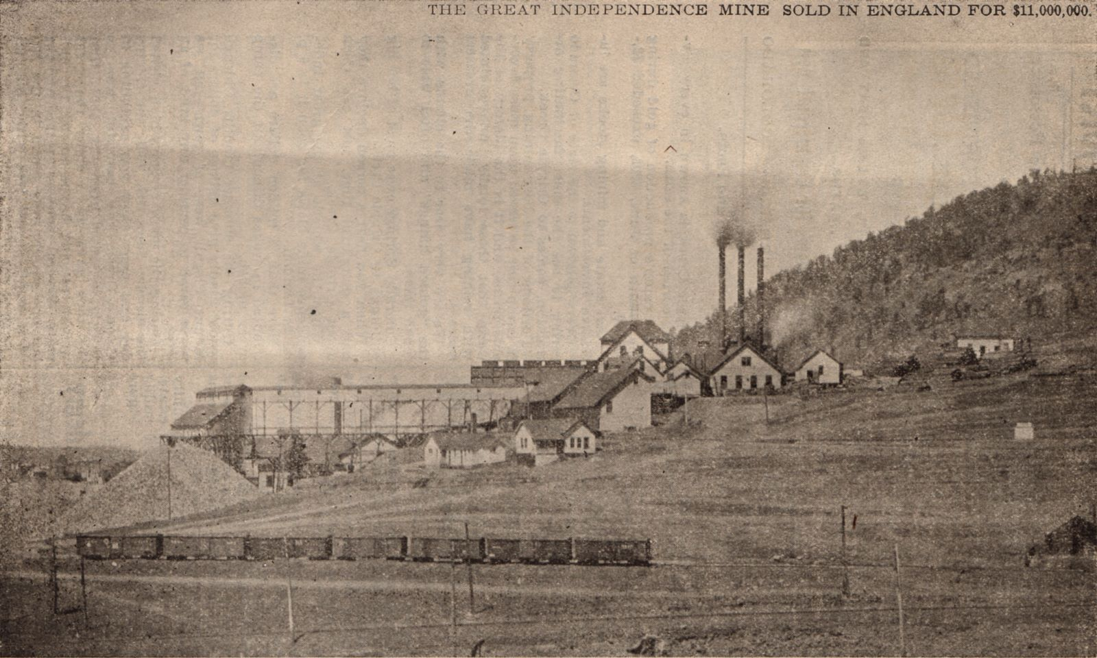 This long distance shot of the large complex known as the Independence Mine is taking looking west with Squaw Mountain background right. In the foreground bottom is the trackage of the Golden Circle with a large string of boxcars set out on a spur. About 1/3 from bottom and from right towards left is the location of the Midland Terminal trackage that was later connected with the Short Line trackage that might be running at the bottom of this view, outside the view I would then presume.    There is many structures and ore-houses at this mine, the one furthest to the left, attached with a long-covered trestle, was also an experimental mill I think.