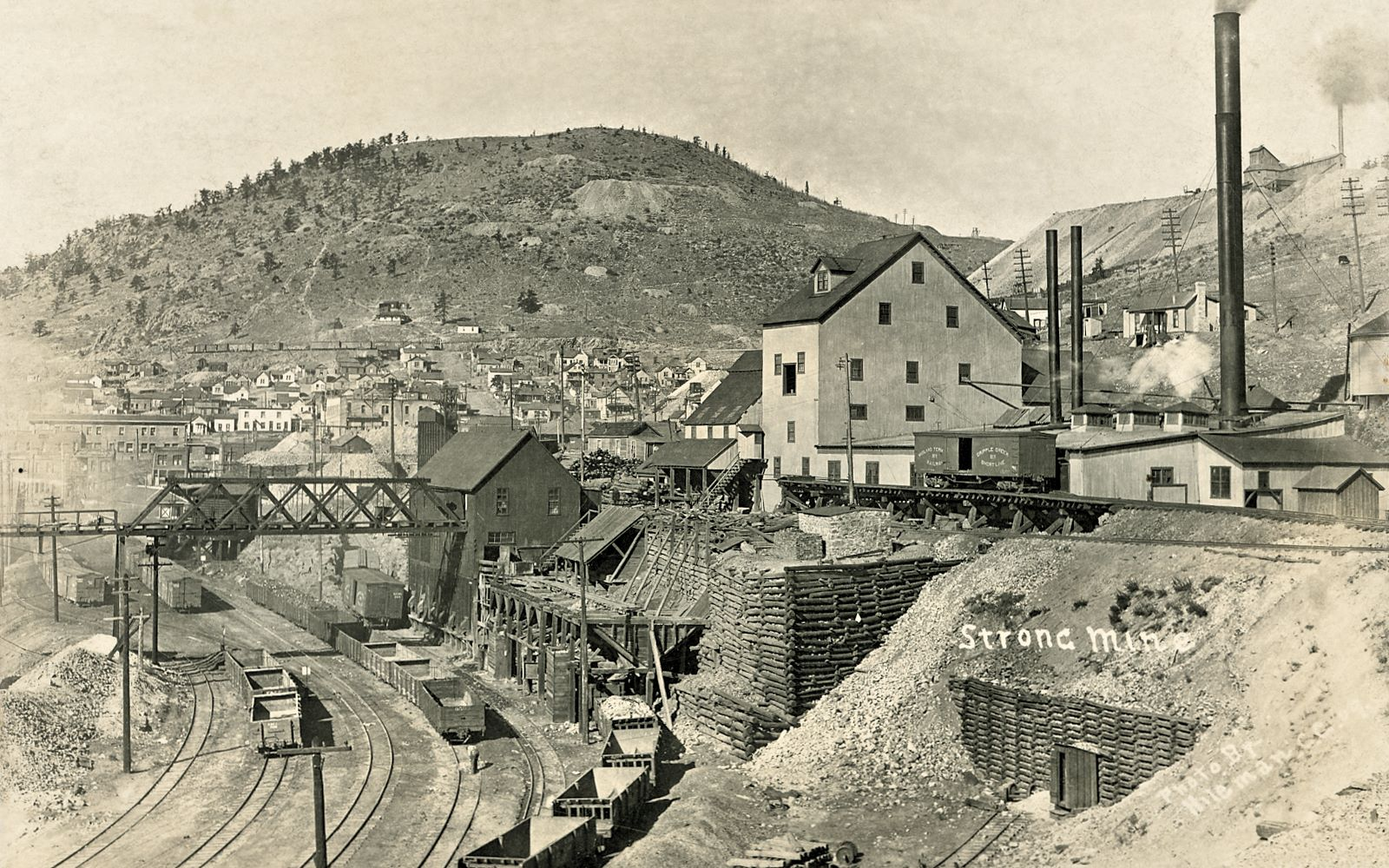 This view of the East & south side of the Strong Mine is quite a good one to tell how it looked sometime in 1909 when T.J. Hileman took the photo which was the base for this postcard view presented here. Down left is the yard of the F. & C.C. railroad, with its dual gauge tracks connected with the M.T. running passed the Ore-House of the Strong Gold Mining Company. Also, the mainline of the Victor branch of the M.T. is shown entering the scene along the right-hand side, where there is shown most of the side-spur for delivering coal to the powerplant of the Strong Mine for their operations, seen here with a single M.T, boxcar (no. 211) parked on the trestle, while the mainline where passenger trains were running is seen this side of that trestle, dropping downgrade to reach the Depot not seen in this view due to being behind the Strong Mine Ore-house.    The Ore-House also has an open-air Ore-Bin type of structure to the east, where Gondola & Hopper type of railroad cars was run under to collect dump materials to be used for railroad work I assume. Also shown is the big truss bridge coming out of the Strong Mine Ore-House, extending across the F. & C.C. yard unto another smaller bridge and taking it to a rock-house outside this view which delivered dump ore to Short Line cars to be used as ballast, fill-mass and similar along the lines, from what I have understood it as.    Just left of the single boxcar at the Coal-room part of the Strong mine, out on the crib-wall part left of the M.T. mainline is seen a small stone structure which Sanborn Fire Insurance Maps for Victor 1908 (sheet 0) say is the Powder Thawing House.