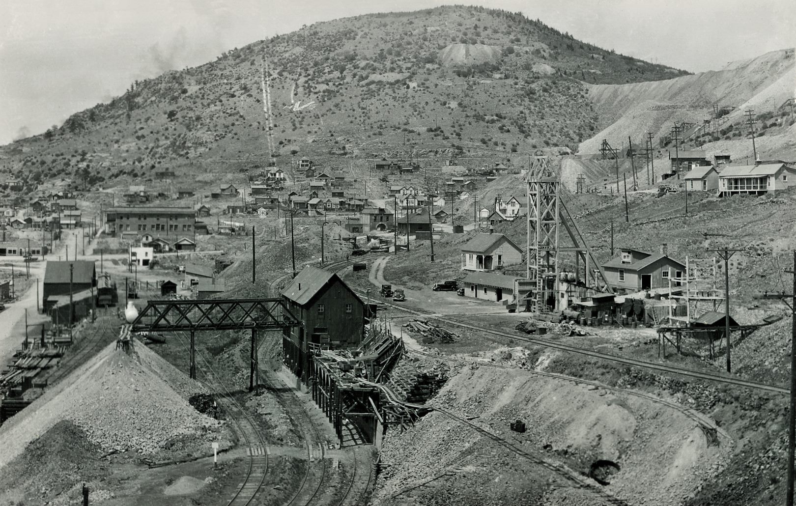 This view of the East & south side of the Strong Mine is quite a good one to tell how it looked sometime after the early 1920's and before the Midland Terminal got ripped out in the late 1940's. Mine is easily seen with its exposed Head frame and Ore-House in the foreground right, showing mine tracks crossing the Midland Terminal between the Head-Frame and the Ore-House. I found this image helpful to me to understand better how the railroads changed over the years as this view do show how the old narrow-gauge yard of the F. & C.C. has three lines of standard gauge tracks on them, coming down the old Switchback connection passed the Strong Mine Orehouse.    Sadly, the left side of this view is more blurred then the rest, seen very easily on the higher resolution scans. I can see there are some railroad spurs there, and it looks like there is only a road surface on Diamond Avenue which dates this to be after the street track of the Trolley was ripped out, otherwise I should have been able to get a glimpse of tracks on left-hand edge about 1/3 up from bottom left.