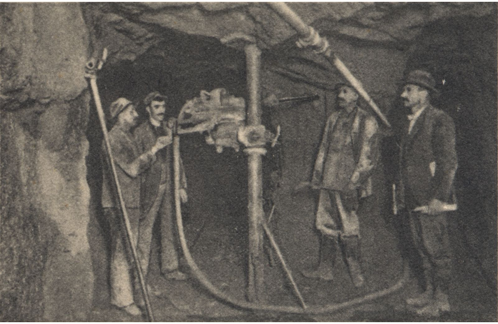 This underground view is from the 700-ft. level of the Gold Coin Mine in Victor. It shows four people, possible 3 miners and 1 foreman of some sort as he looks much nicer in his clothing then the other three. The well-dressed man holds some candles in his hands. There is two tunnels seen, a pipe is hanging near roof and comes out from the right-most tunnel, where also a hose is laid to a drill machine put up on a pole, fasten to floor and ceiling of the tunnel opening. All four men is looking at this machine, posing for this photo I assume.    Pikes Peak Library has a much better view of this photo then my copies can present.