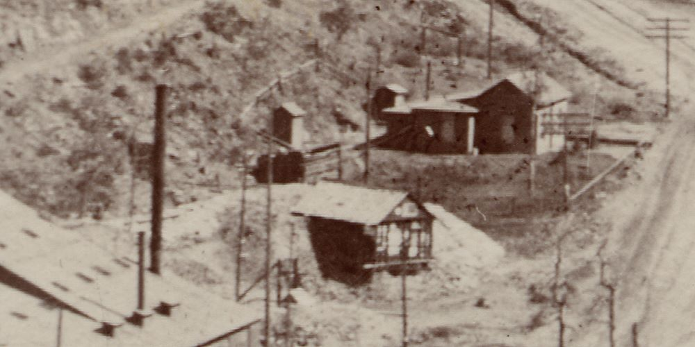 This cropped view from an unmarked Stereoview, showing the town of Anaconda with the School House and the Hartzell Mill in the foreground, has part of that mill seen in lower left, with the Ore-house of the Blue Bell mine just to the right, and the entry to the Blue Bell Tunnel hiding behind the smokestack of the mill.