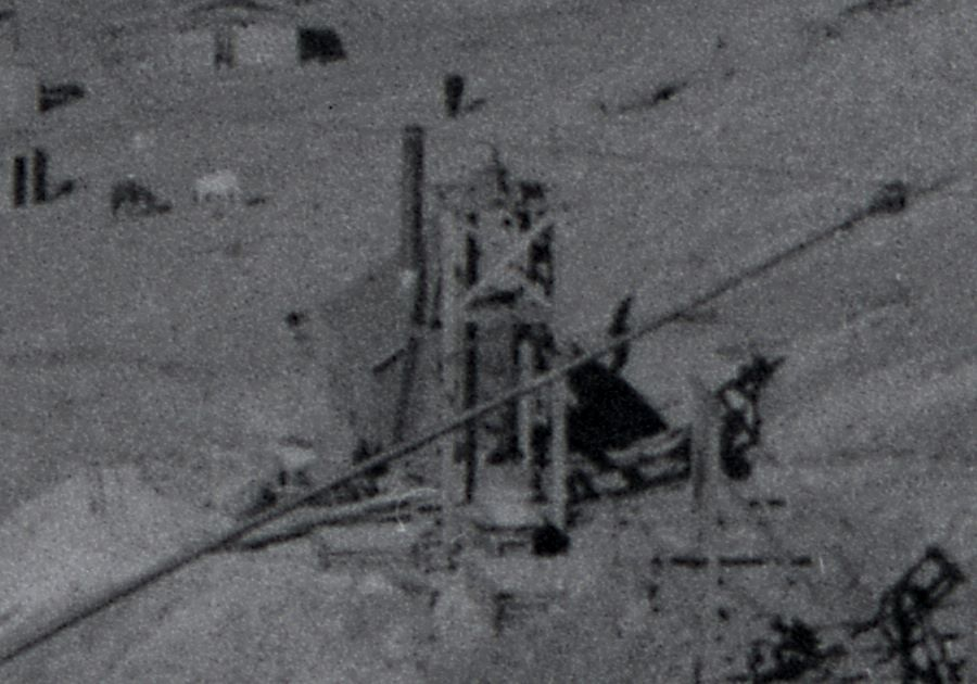 View is a negative type of Photo taken by a camera of an older type of Photograph, with not the best quality film so it is rather grainy sadly. Cropped from a view of the Trolley car named Grace climbing Gold Hill high above Poverty Gulch, along the original steep High Line grade, part of the back trolley pole is seen coming in from lower left-hand corner poking into the image towards upper right-hand corner. * The May Queen Mine is seen center with its Hoist House and Head-Frame in front of it, while in lower right-hand corner is seen part of the head-frame on the Granite Hill mine.