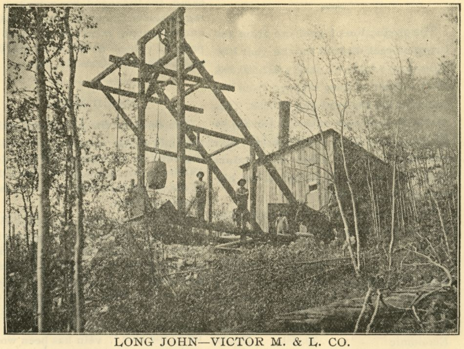 A view uphill at the mining operations of the Victor Mines & Land Company, and their work on the Long John mine on Ironclad Hill. Men pose under the head frame with a bucket hanging over the shaft and the hoist house with a smokestack is seen just to the right of the head frame.