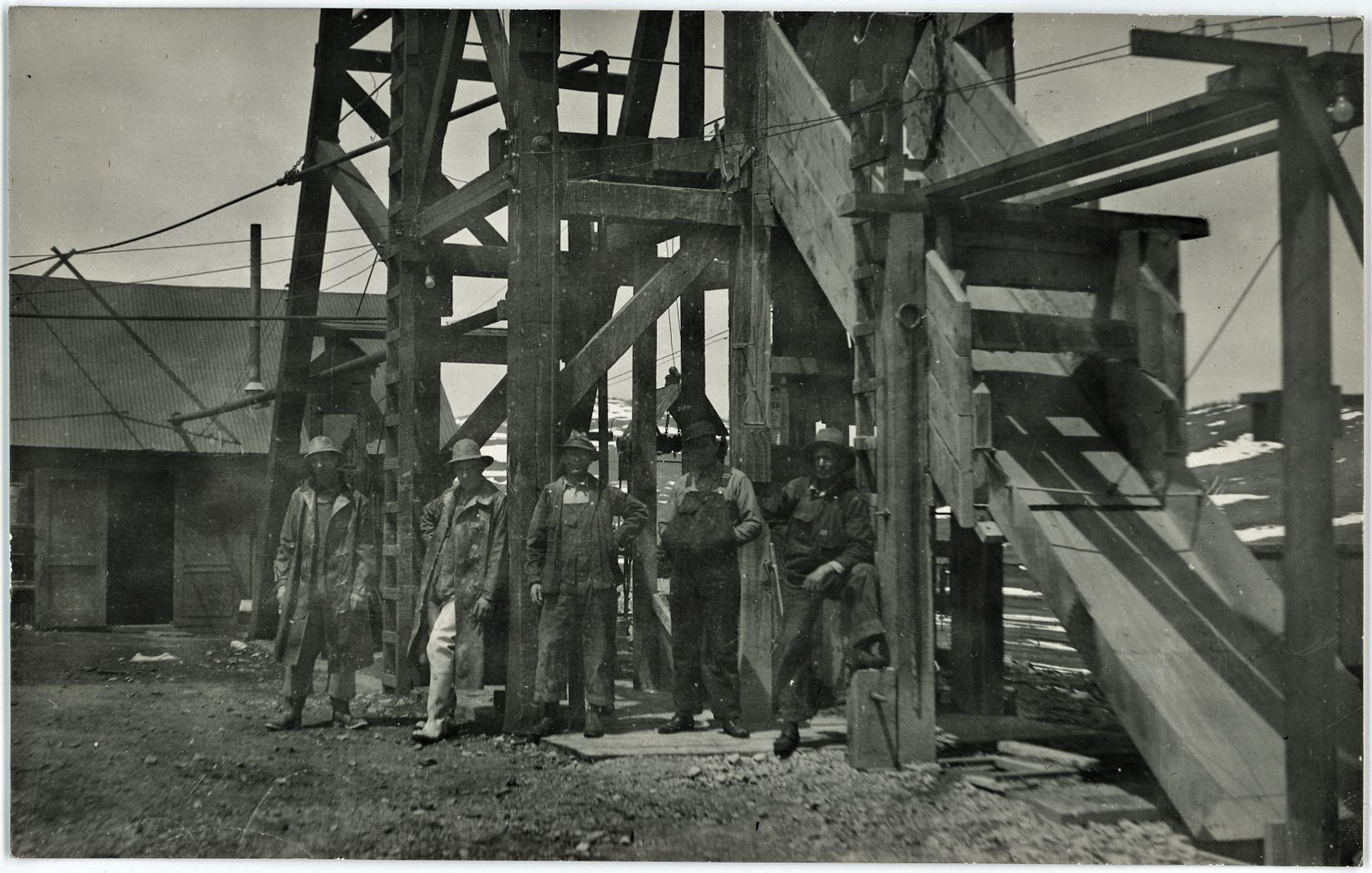 This enhanced view of my 300dpi scan of the source postcard shows some of the surface structures at the Cameron Mine, where 5 men are posing for the photographer, standing in front of a Head-Frame, with the Hoist-House and shed type of structure in background left and a chute down from the Head-Frame in front right. I've seen a marked postcard with the same head-frame and hoist-house look as here, hence the strong feel this being the Cameron Mine, located in Cameron/Grassy Valley in the District.