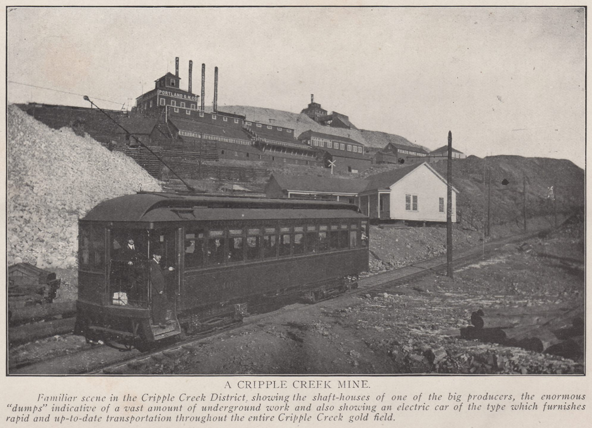 Familiar scene in the Cripple Creek District, showing the shaft-houses of one of the big producers, the enormous ''dumps'' indicative of a vast amound of underground work and also showing an electric car of the type which furnishes rapid and up-to-date transportation throughout the entire Cripple Creek gold field. -> This is along the original High Line, just before it crosses over the M.T. mainline on its way down Battle Mountain. The mines in the background is the Portland Nos. 1 & 2.