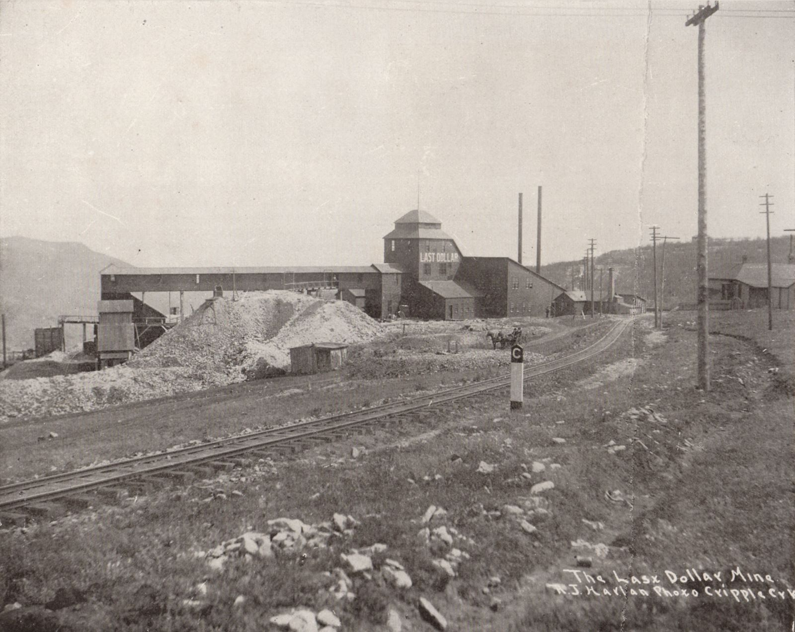 This view of the Last Dollar Mine is photographed same day and time as a more common seen view from nearly same location, where the photographer Harlan as moved closer to the Golden Circle trackage seen near lower left corner, to avoid that telegraph pole in the foreground near right-hand side. In both views, there is a man dumping an ore-car about 1/4 in from left-hand side on this view, in front of the covered gangway from mine to the ore-house seen near left-hand side. The ore-house was connected to another Golden Circle spur, which also went on to other mines around the town of Independence, while the track in the foreground is the mainline going towards Victor mine high up on Bull Cliffs/Hills.