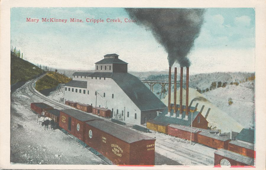 This image is showing the great Mary McKinney mine in Anaconda with lot of railroad traffic in front of. It shows the business side of the mine in terms of where the coal is brought in for power the mine, and where ore is taken away. Both in and out uses boxcars, the power plant is seen at lower right, with a string of boxcars in front of it. Further on another 3 boxcars are put up to load ore from the mine plant itself, along a spur that used to be dual gauged as both the M.T and the F. & C.C. used this spur to serve this mine. After the closing of the narrow gauge this spur was used to get access down to the El Paso mine way outside the view to the left. Town of Anaconda would have been down the valley at right. Also, in front left another side spur of the M.T. is used to load more boxcars with ore from surrounding mines on Guyot Hill via transfers from horse pulled ore-wagons – which would have been the way most of the mines did transport their ores to the railroads.