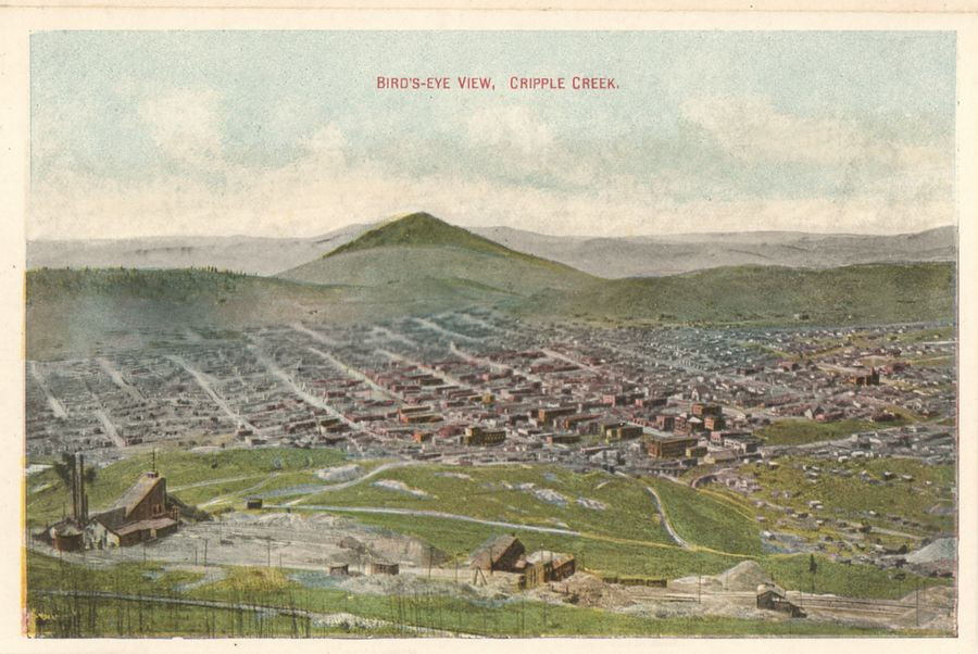 This view and similar angled ones must be the most common view of Cripple Creek I believe! I've seen them in dozens of postcards, photographs in books and other printed mediums, and in at least a couple of variations. While this particular edition is by time of writing (28.03.2018) known to me with 12 uses ranging from postcard folders to postcards them self, but I don't have an overview of uses in books except for a very few books, so I assume that number will grow larger if I ever get around to make list of images used in all books I've seen.       In foreground left, about 1/4 up from bottom and about 1/7 in from left-hand side is the surface structures of the Moon-Anchor mine, with the roadbed of the High Line electric, and the Short Line railroad, on this side of the structure, even if this is not the best view to pick those out though. Near Bottom of the image the original High Line Electric roadbed is seen climbing from left and disappearing about center sideways at the bottom. Can also be seen coming uphill from almost bottom right, where if the view had been a better one, one should have seen both the Trolley Line and the Short Line tracks run uphill from right towards left.