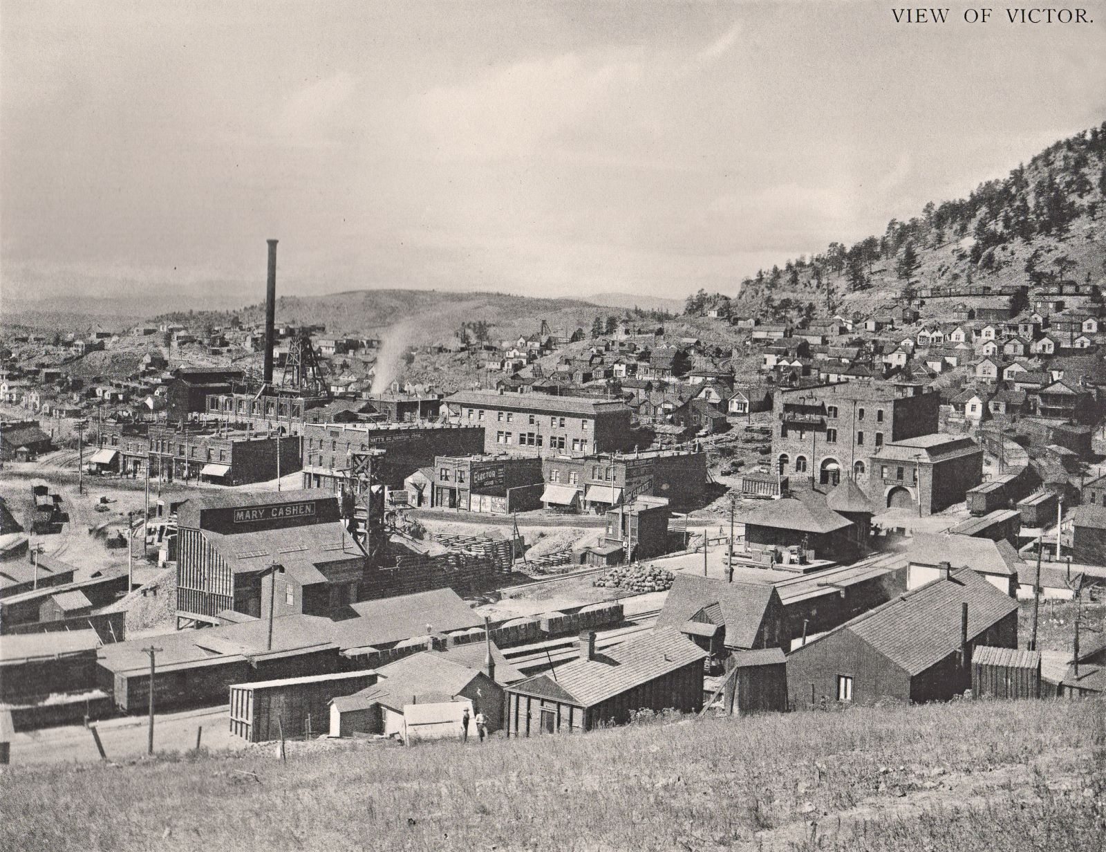 This interesting view from Battle Mountain towards the Gold Coin mine in Victor, as it is getting rebuilt after the 1899 fire that destroyed the old mine and lot of the town itself, helps give the impression of what was first rebuilt and what was postponed. The Ore-house was clearly important as that is already up in this view, same is the large head frame, while the shaft house only have the first level of walls put up. In the foreground is the distinctive Ore-house of the Mary Cashen seen, with its head frame just to the right of the orehouse.  Victor Public Sampler is the long structure in-front of the Mary Cashen, and the railroad in the foreground is the M.T with its depot towards the right-hand side of this view.