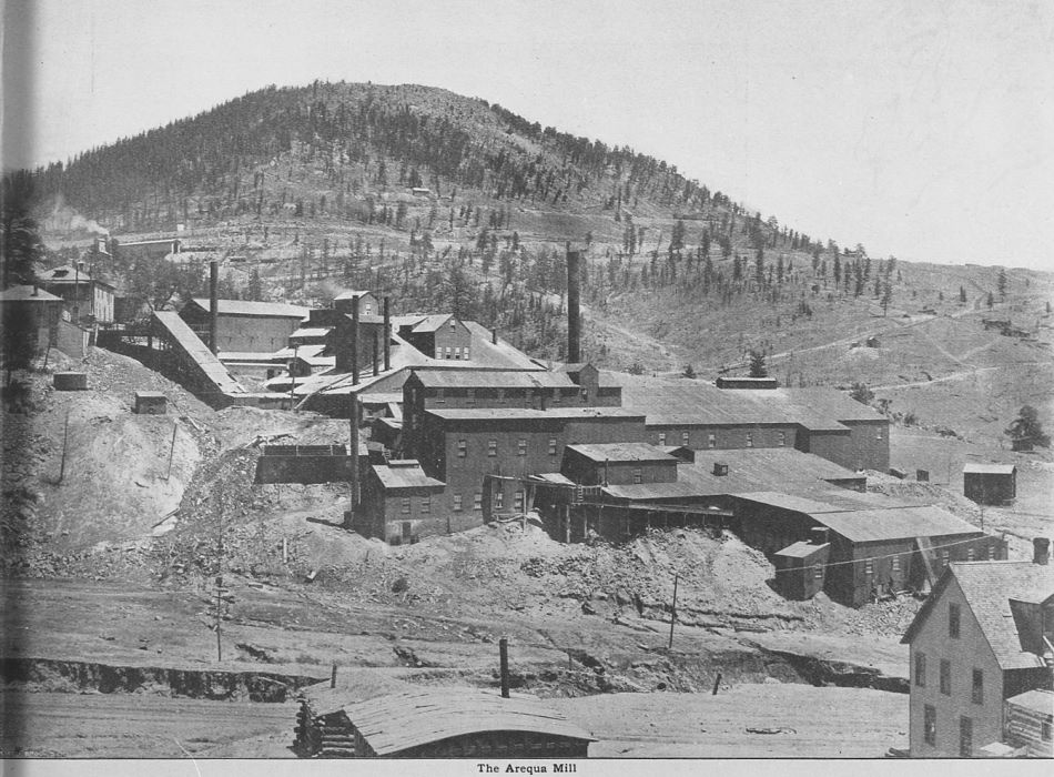 This view shows a large mill operation, it must have been quite a look to see this in person, a mill built upon over time. In the background, about 1/3 down on left-hand side from the top, you can see the ore-receiving shed of the large Economic Mill, with part of a cooling tower poking up as well. Squaw Mountain is looming in the background, together with some mines and railroad grades of all three railroads serving this District.    The view of the Economic mill and the Low Line dates this view to have been photographed between 1900 and middle of April 1903. Reason for that end date is I read the Arequa mill was fully destroyed by a fire in the Engineering & Mining Journal, published on the 18th of April, 1903.