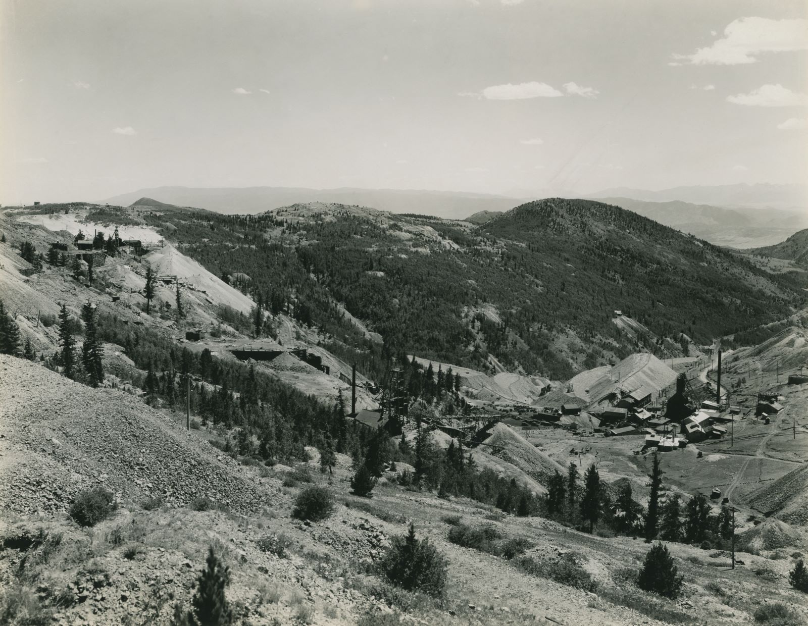 This photo is from the western slope of Bull Hill, looking towards south, southwest near the John A. Logan mine. Down in the valley on the right-hand side of this image is the Cresson Mine, while about center sideways and 1/3 up from bottom is the Head-frame of the Gold Sovereign Mine, with the ruins of the Trilby Mill/Mine further left and a piece of the Gold Sovereign Branch line off the High Line seen climbing the hill below a big dump from one of the Dante Mine shafts seen near left-hand side about 1/3 down from top. The hill seen about 1/3 in from right-hand side is Squaw Mountain, and on the slope down into Eclipse Gulch is seen the mine operation that I think would be the Carbonate Queen. Seen about middle top/down and about 1/4 in from right-hand side.