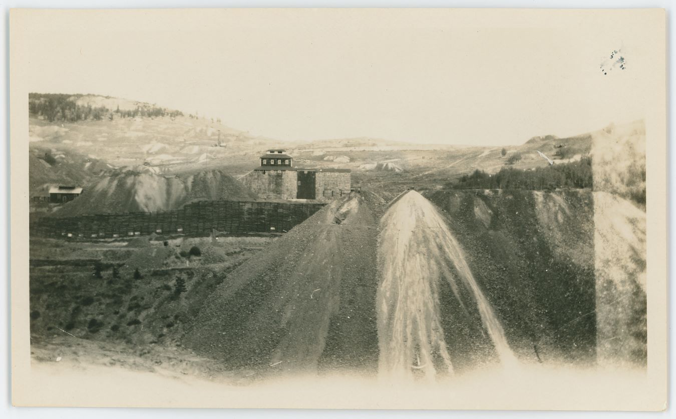 This view from August 1928 is not the best view I've seen, but being dated it do help tell how this area looked at that date in time, and that is always nice. The photographer took this view looking south across Squaw Gulch towards the Huge dumps of the Mary McKinney Mine, seen behind the dump, the Crib-Wall, and with Raven Hill making up the background left. There are smaller dumps on Raven Hill, and one single head frame is seen, not fully sure which mine this was part of, I know the Work Company mines was in this area, but this mine head frame name escapes me at this time.