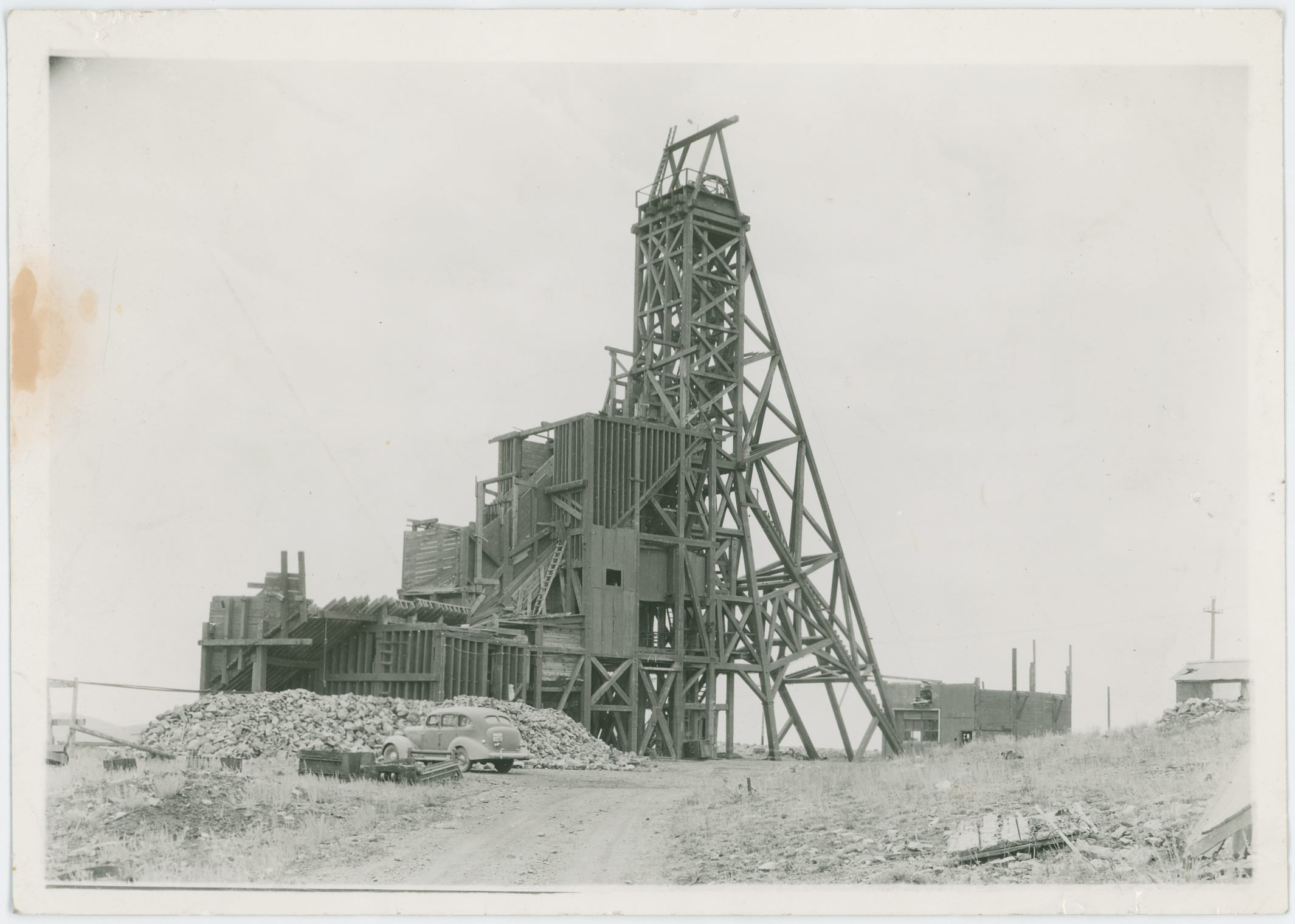 I think this is from around 1940, but I do not know. There is a car parked below this view at the exposed Huge Head-Frame/Gallows-Frame of the old Stratton Independence Mine on Battle Mountain, outskirts of Victor, Colorado, and that seems to have a License-plate of 43-660 but I can't tell what else it might have written above the numbers, so I can't date the image from that either…    The whole structure is quite massive, and all in wood it appears! Hard to imagine all this at one time enclosed in a massive Shaft-house type of structure, as I assume this is as it was built inside the structure back in the days. The left most parts, with the various bins I do think is more recent then the headframe itself, but I dare not say anything as this is beyond my knowledge.