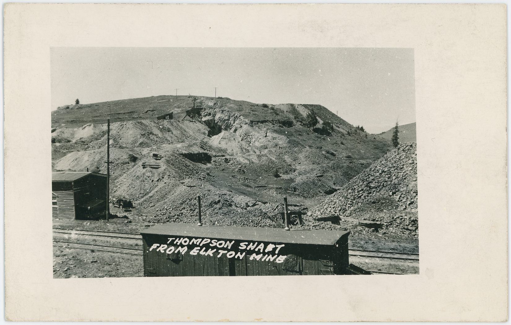 This postcard view of the Thompson Shaft from Elkton Mine sort of helps in telling there was a mine on the Thompson claim where the M.T. switchback up to the Elkton coalbins had its switch.  One can see part of the lower leg of that spur poking up in a fill on the left part of the view - sort of between the two structures seen in the foreground. Head frame is seen behind there again, and a large cut in the rock making up this hill is seen just right of that mine.    Seen in the foreground is the M.T. mainline tracks, which passed the Elkton mine, and who would be to the right and behind the photographer.