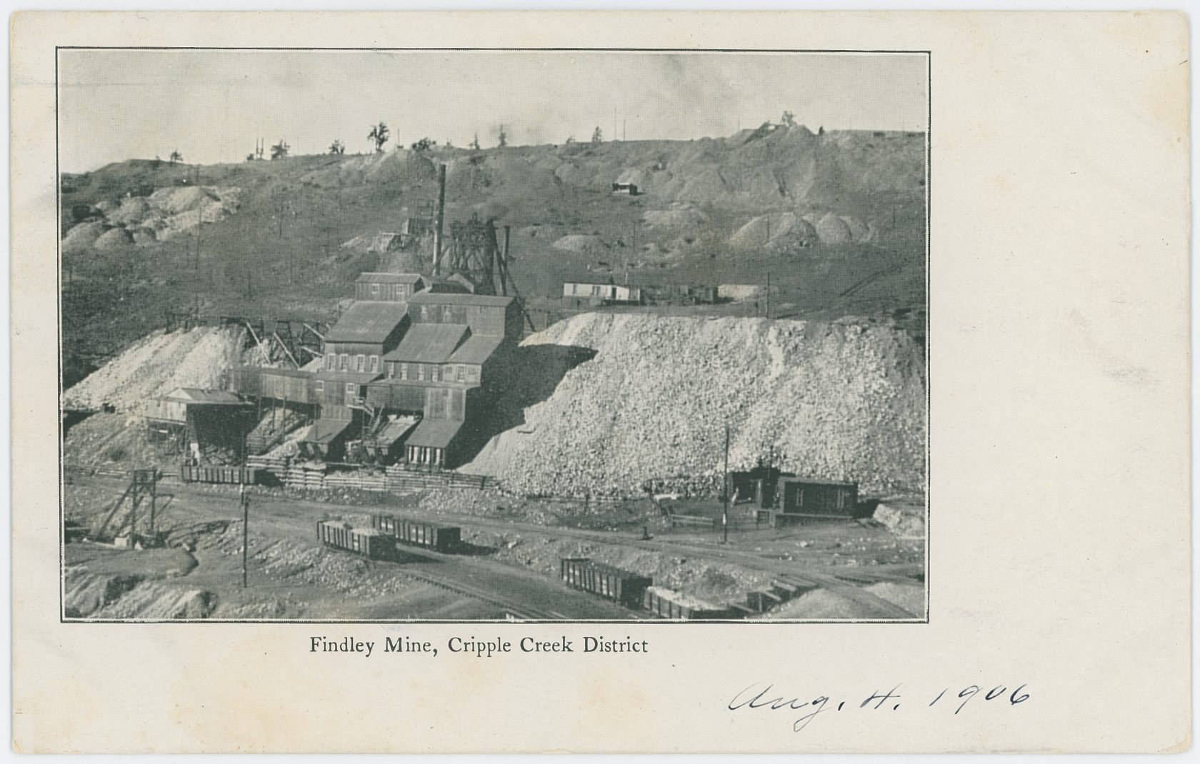 I never seen this view as a photograph, only as the printed image used for this postcard and two kind of postcard folders, where there where small images included inside one larger postcard view. This is a nice view of the large operations going down at the Findley Mine, with several smaller dumps seen in the distance, all on Bull Hill, looking westerly.    In the foreground several railroad cars on spurs belonging to the Golden Circle 3-foot railroad can be seen, and I would suspect the home seen in lower right is considered to be part of the Independence townsite even if I can't really see the town itself as that is outside the view at bottom.    The first two tracks from bottom up is sidings used to collect ore from horse run wagons from the many smaller mines in the area, while the spur just going to the bottom part of the right-hand bottom corner is a spur I've seen being connected to mine named Deadwood No. 2 if I've read images I've seen correctly. While the track going of into the right-hand side of the lower right bottom, that is part of the Golden Circle mainline that used to run passed the Independence Depot and unto the end loop at Vista Grande, sort of outside the view twice the width or so of this card to the right, higher up, behind the hill.