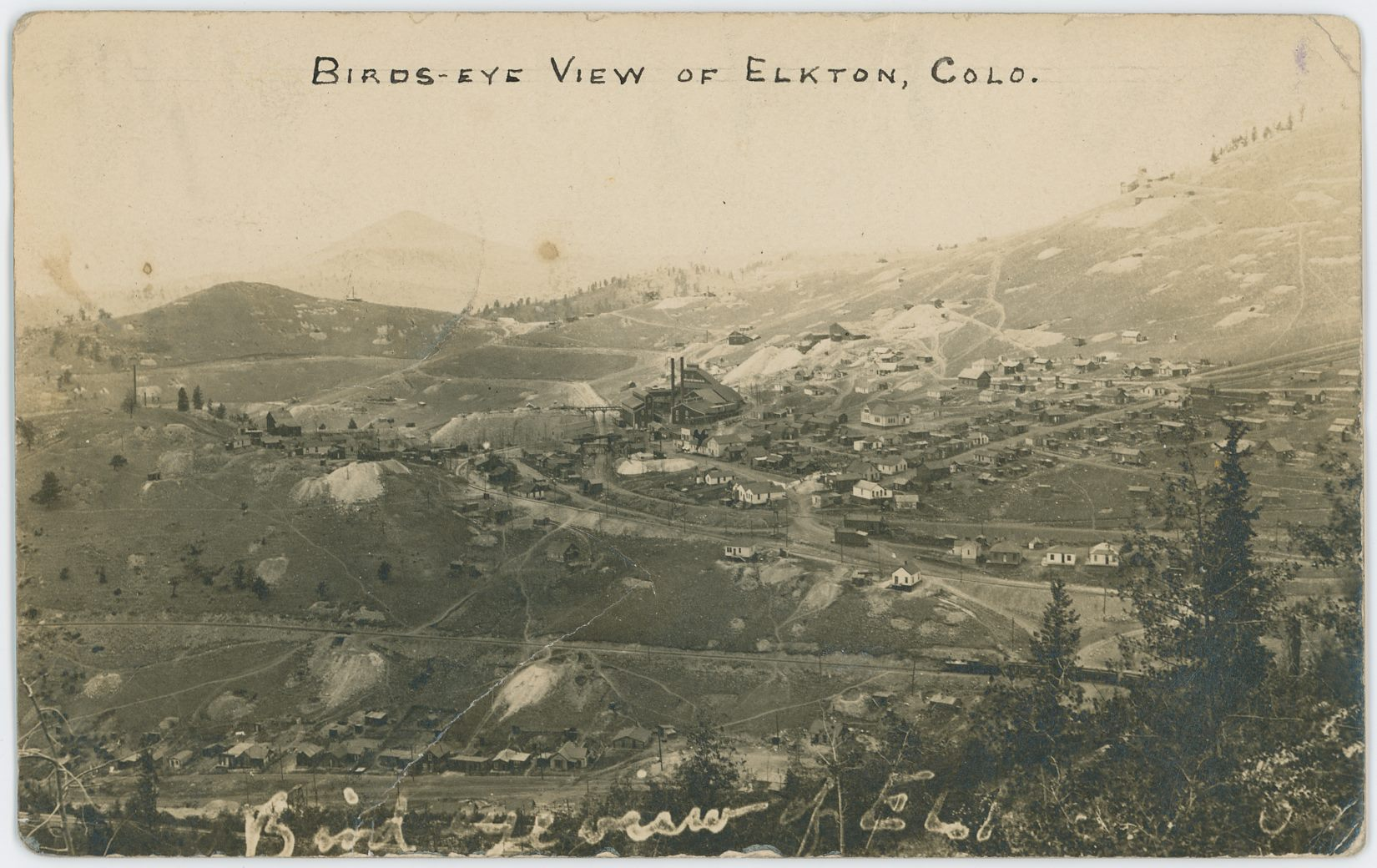 While the image quality is not that great due to the age and distance and all that, it still is a very important image to have! I struggle a little dating it as while it has a post stamp of 1908, I am unable to find the switchback from the M.T. up to the coal bins of Elkton Mine, which is shown on a USGS topographic map dated 1902/1903, which together with the showing of the Low Line which dates this after 1900, should narrow the timeframe down quite much, but the Elkton Mine structures gives me the impression this is way later then near 1900.    This due to the fact Sanborn 1900 (CC Sheet 17) shows a different structure here, while photo matches better with Sanborn 1908 map (CC Sheet 30). But then again, that later map fails to show some of the mine structures seen here so that suggest this view predates it. And as my USGS map show a spur not here I must admit that this is from a timeframe of less than 3-years. More research is needed.    Near bottom of this view lays a row of houses which forms the upper part of the settlement know as Eclipse, along Eclipse Gulch, stretching from about where F. & C.C. crosses the gulch and to around where the Economic Mill was further down the gulch at left, as far as I know.    The grade of the F. & C.C. is seen about 1/4 up from the bottom, with a passenger train near right-hand side, heading towards Cripple Creek. There are several mine operations seen below and above that grade, but my knowledge is way too limited to tell anything about any of them.    The town of Elkton is seen on the lower slope of Raven hill in the right-most half of the photo around middle of view top/down, where the large Elkton Mine makes up about center of this card, with the railroad grade of the M.T. running just left of the mine.    The Low Line is seen about 1/3 up from bottom near right-hand side, climbing the hill towards left and about middle top/down and about 1/3 in from left-hand side it changes directions and goes towards right, cross over the M.T. on trestle and passes the Elkton mine on the right side.    The Thompson large Shaft House (I think) is seen about center of view top/down and about 1/5 in from left-hand side, sadly I don't know of any Sanborn map of this structure, not that I can recall at the time of this writing [08.08.2017].    There is also another mine structure at right foreground of the Thompson, left of the Low Line grade, but I dare not guestimate a name for that mine, nor do I dare take a stab at the name of the ones seen inside the town of Elkton either. One is easy to spot, just right of the mainline of M.T. with a large dump area, the other is more hidden among houses, still with a dump though. One day I hope to learn all this, one day.    Raven Hill has it shares of mines as well, but the one I sort of care about is the Bostwick Shaft House, seen about 1/3 down from top and slightly right of center of view sideways, up from right-hand side of the Elkton mine.