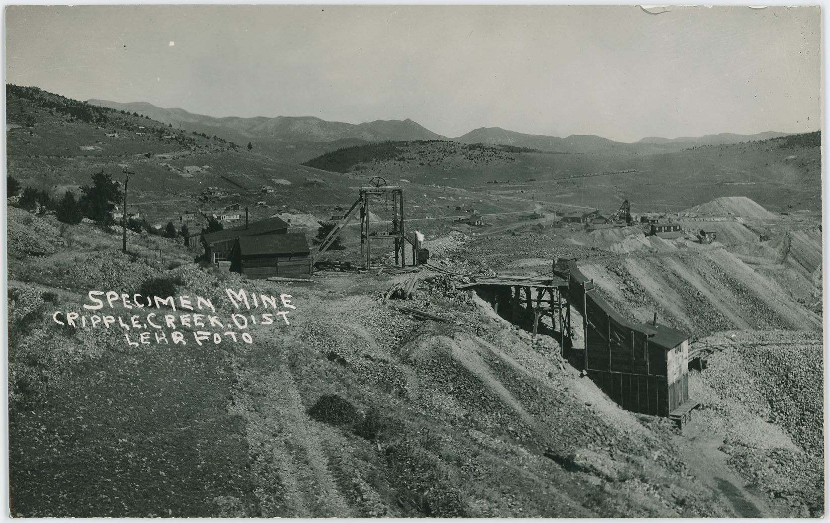 Direction of this view is east, northeast, on Bull Hill, just west of the surface structures of the Specimen Mine operation, with an open Head-Frame and Hoist-house and shed linked to it, and a small Ore-house to the right down the hillside a small bit.    In the distance, up from the orehouse, the surface structures of the Vindicator No. 1 Mine are seen with a large Head-frame and Ore-house down into massive dumps, impossible to tell if it still is linked to a railroad or not in this view. Further on in the distance to the left, a big string of railroad cars say that the Midland Terminal is still in operation, but there is no trace of the High Line Electric Division, as where that should be I only see a road surface – cutting almost the headframe of the Specimen Mine in two so to speak.    Image is not sharp enough to tell if there are any rails left on the old Golden Circle tracks seen climbing Bull Hill, or is it Bull Cliff, about 1/4 down from top and about 1/4 in from left-hand side, but I do think the standard gauge M.T. tracks are there still when this photo was taken by Lehr many years ago.