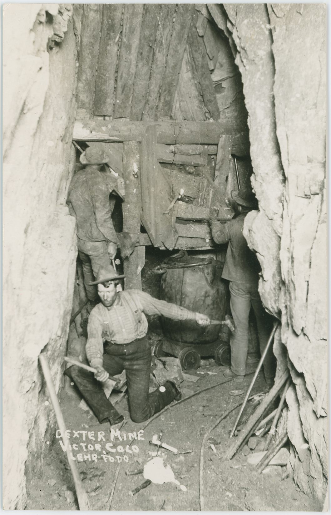 I've seen this view as two postcard versions and one photograph, but none of them has given anymore info then that this is someplace underground at the Dexter Mine on Bull Hill, no level info ever been given.    The view is of 3 miners sort of posing for a photo at a chute with a at the corner of a curve in the underground works. One man is sitting partly on his knee and is working a hammer and chisel with his left arm holding the hammer unless the photo is a mirror copy of the original scene, as I've seen happen before in other images. The other two men has their backs at the photographer and seems to be working the chute to fill a bucket sitting on top of a wheel setup pulled away from the rails.