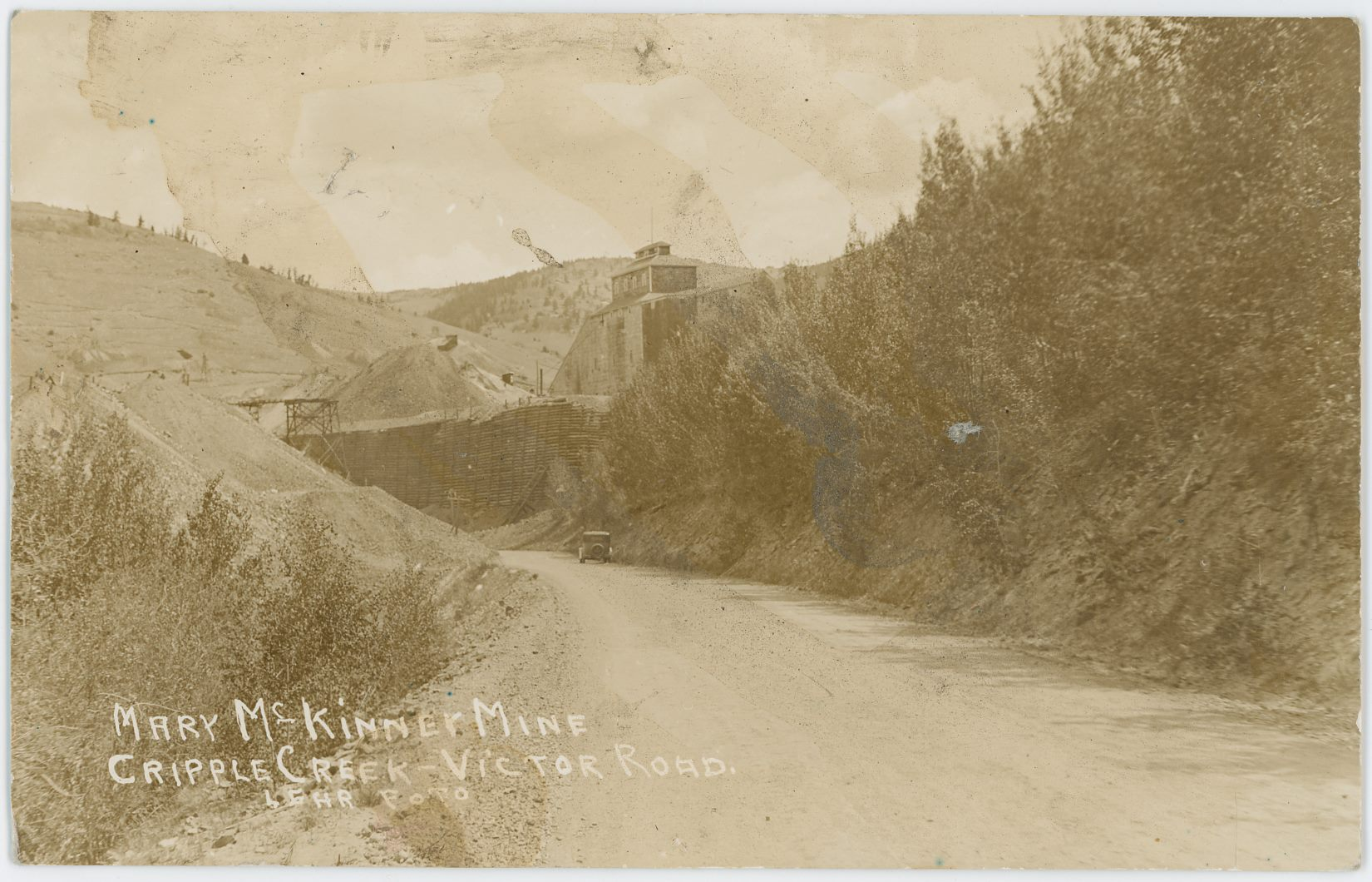 This view is from along the Victor-Cripple Creek road, running on the former roadbed of the Florence & Cripple Creek, looking towards the Mary McKinney Mine about center sideways and its huge crib-wall. If one could have walked into the view and hitched a ride with the automobile seen one would have ended up in Cripple Creek.    The Hill in distance left-hand side is part of Gold Hill, and I wonder if part of the old Short Line roadbed is visible up there near the skyline. I can't sadly see anything though in a high-resolution scan of 1200dpi, as there is just too much blur, and overall the whole card is sadly not in a good shape due to someone at some time in the past having spilled something over it.