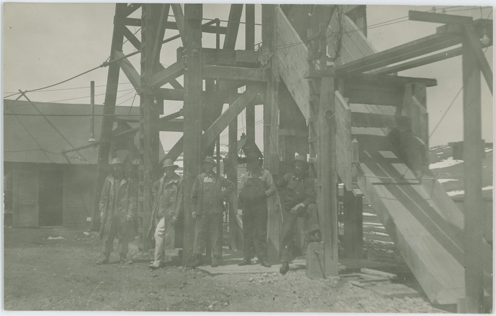 Another image I did not know where was at the time I bought it, but which I still wanted. And while I have this little bit uncertainty in me still, I do however strongly feel that this is at the Cameron Mine, where 5 men are posing for the photographer, standing in front of a Head-Frame, with the Hoist-House and shed type of structure in background left and a chute down from the Head-Frame in front right. I've seen a marked postcard with the same head-frame and hoist-house look as here, hence the strong feel this being the Cameron Mine, located in Cameron/Grassy Valley in the District.