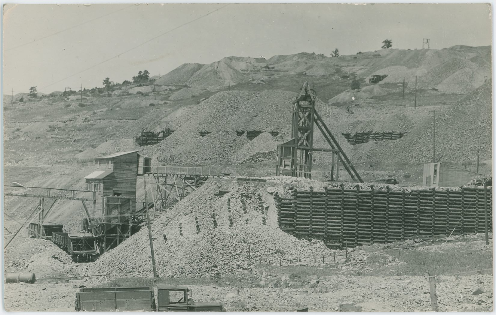 This is a view at a smaller Mine operation at the location of the former larger Hull City Mine, the cribbing seen further uphill in the background was part of the large Findley Dump. What happened to the much larger and well-known Hull City Mine I have no knowledge about, maybe it burned? Maybe it got tore down?    * About 2/7 down from top and nearly 1/7 in from left-hand side, against the sky, is the top of the Head-frame at the Specimen Mine seen with its wheel about center of the top frame from right to left in this view – very hard to make out on the postcard scan, easier to see on my 1200dpi scan.    * About 1/7 down from top and about 1/7 in from right-hand side is another Head-Frame seen, and I keep wondering if this might not be the eastern Lucky Guess shaft? Very hard to tell, the old shaft house is long gone.    * The old Golden Circle Mainline is seen about 2/5 down from top, entering the view at left-side, climbing a little, hide behind a dump at the crib-wall, then being visible a little again before exiting behind a new dump at the right-hand side. Below the crib-wall, almost at middle down/top is the old grade of the High Line, and the Short Line Portland branch – long gone in this view as I see no line side poles, so this help dating the view to be after the demise of the Trolley Service in late 1919.    * Sanborn Fire Insurance Map for Victor dated August 1919 (Sheet 10; Independence) shows the more common old larger structure at this location, so I do think this view is way later but have nothing to compare it with.