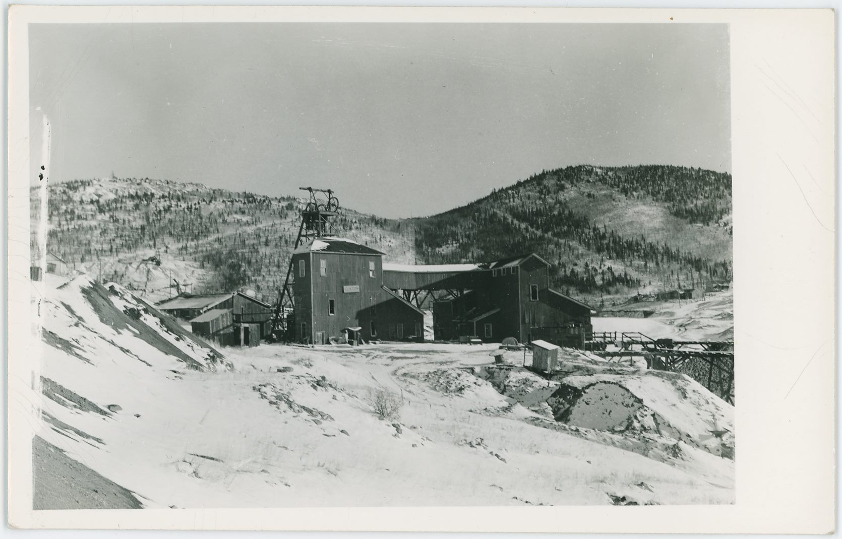 A winter view at the partly exposed Head-Frame part of the Elkton Mine on Raven Hill, looking from the north and west side. Snow covers the ground and in the background is the saddle between Battle Mountain on left and Squaw Mountain on right if I am not mistaken.    * The Carbonate Queen Head-frame and surface structures are seen in the background left, about center top/down and about 1/5 in from left-hand side. Quite some dumps in that area it seems.
