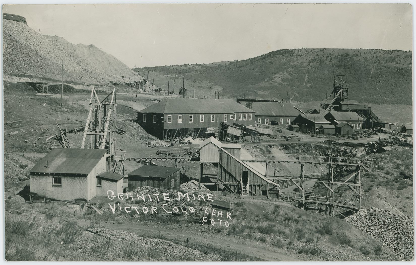 Scene shows the smaller more 'modern' Granite Mine as it was looking at the time of the photo, with the dumps of the Portland No. 2 in upper left and the Lumber Work House of the Portland No. 1 seen about 1/3 down from top and center sideways, while the Head-Frame is seen near right-hand side. The old grade of the Golden Circle ran in the 'cut' seen in lower right quadrangle – having come out from the Steel Tunnel below the Portland No. 1 dumps, part of the crib-walls is still seen in this view.    There appears to still be track on the Short Line Ajax branch as well, seen below the Portland No. 2 dumps in upper left, track is seen about 1/3 down from top, from left-hand edge to about 2/5 into the view towards right, where it curves out of out view.