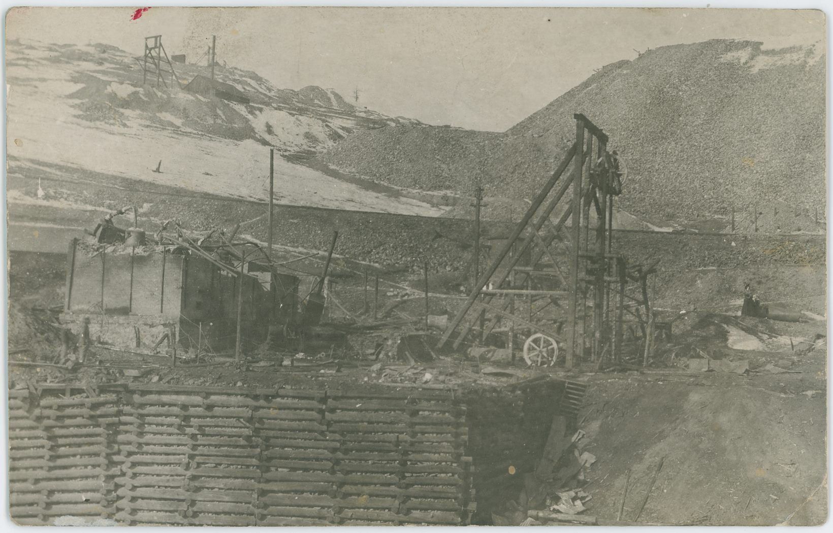 This is a view at what was left of the Granite Mine after the explosion January 8, 1911. Or possible some days/week after, not sure if the Head-frame is put up after wrecking of the original one, or if this was what was in use at time of the explosion that wrecked the Engine/Hoist House seen at left side.    The crib-wall seen in foreground is holding the ground back from the Golden Circle trackage that ran in the cut at the bottom. While behind the headframe is seen another railroad track, almost halfway down from the top on the right-hand side, this is the Short Line Ajax branch-line.    Dump at upper right I assume is part of the Portland No. 2 dumps, while the mine seen more to the left near top of image is at the moment of writing this [28.05.2018] a mystery mine to me, actually both, as there is one more even higher up…
