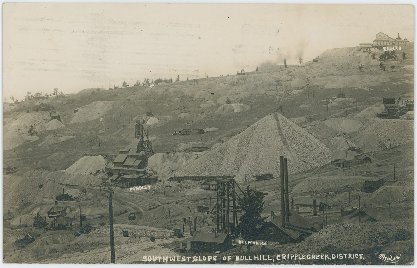 This view at mining operations on Bull Hill, is hampered sadly by the fact that the paper this postcard is made on is one of those not so good one, and while it scanned useful it is not very good as the dark areas are just dark, and there is some silvery like parts in those darker area, also messing with my scan.    The scene itself is an interesting one, as it captures and identifying some of the mines at this area of Bull Hill, also shows the Golden Circle trackage in this area, with lots of small mine operations around on the ground, with homes and houses spread around and growing huge dumps.    In upper right corner the American Eagle Shaft House and mine operation is seen marked as 'Eagles' while further down along the right-hand side, the Ore-House of the Shurtloff No. 2 Mine is seen about 2/5 down – this had a side-spur, leaving the mainline of the Golden Circle about halfway up the route around Bull Cliffs on the south side, pieces of that spur is seen in lower foreground just above the word 'Cripple' in the card's title text along the bottom of this postcard view.