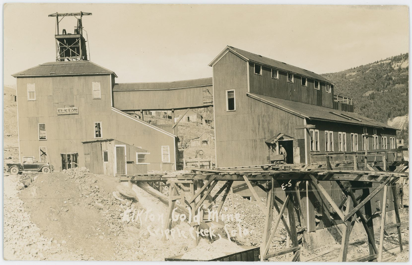 This view at the northern side of the Elkton Mine complex is a quite nice one, but it has faded a little and appears washed out. There is an automobile parked at the old Shaft House where only the north portion of it still stands, the Head-Frame is in the Open air so to speak, but they kept the landing area and covered trestle over to the Ore-House Structure. A man is standing with a small hand ore-car at the door out of the orehouse on the trestlework to the dump areas. There is also a single Midland Terminal Gondola parked almost under one of those dump track trestles.    Town of Elkton is partly seen behind the mine with a couple of houses visible, and along the right-hand side, about halfway up from bottom, there appears to be an Adit/Tunnel Portal into the hillside in the distance which I think would be Battle Mountain in terms of name of the hill, while the Adit I do not know, but this might be part of the Eclipse-Carbonate Queen Mine operation.